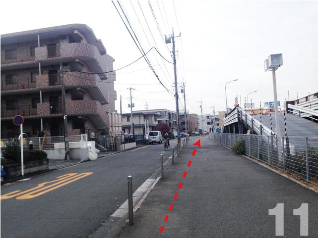 11. 駐車場を右側にして進むと,左前方に,3階建のグレーのマンションが見えます。